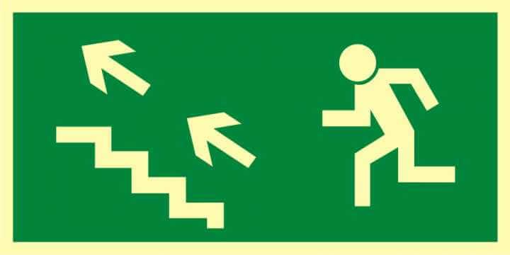 Znak ewakuacyjny Kierunek do wyjścia drogi ewakuacyjnej schodami w górę w lewo