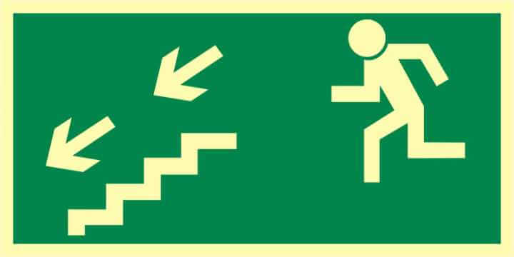 Znak ewakuacyjny Kierunek do wyjścia drogi ewakuacyjnej schodami w dół w lewo